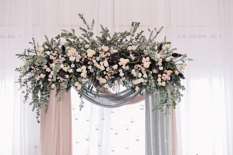 Красивая арка свадьбы Свод украшенный с peachy и серебристыми тканью и цветками стоковое изображение
