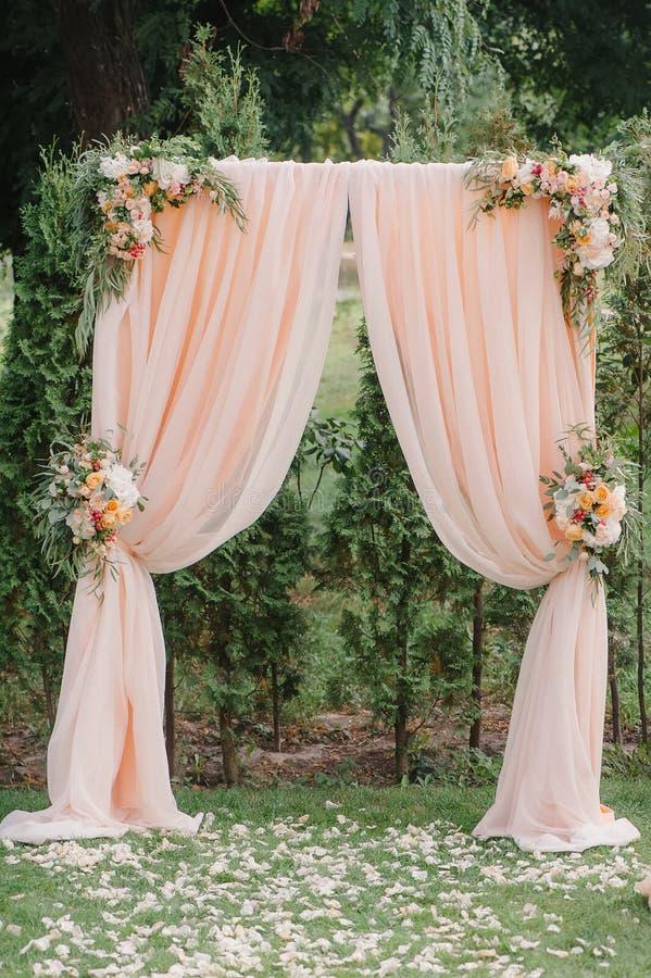 Красивая арка свадьбы Свод украшенный с peachy тканью и цветками стоковая фотография rf