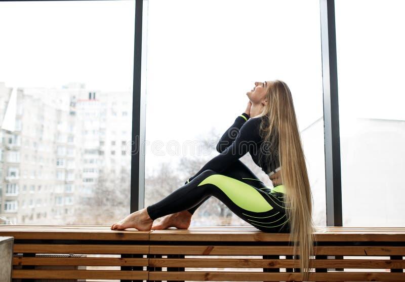 Красивая атлетическая девушка с очень длинными светлыми волосами сидит на деревянном windowsill рядом с панорамными окнами внутри стоковая фотография rf