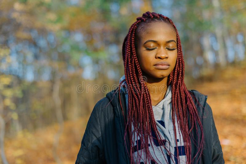Красивая африканская женщина с длинными красными волосами и закрытыми глазами Портрет Конца-вверх Положение парка осени стоковое фото rf
