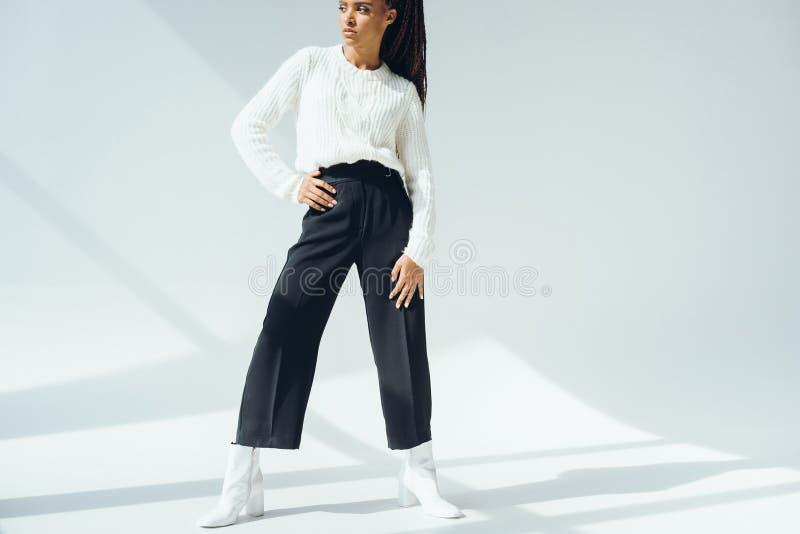 красивая Афро-американская женщина в ультрамодных черных брюках и связанном свитере смотря прочь стоковые изображения rf