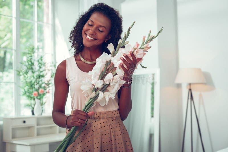 Красивая Афро-американская женщина наслаждаясь красивым букетом гладиолусов стоковая фотография