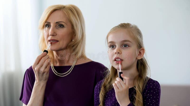 Красивая бабушка и маленькая внучка прикладывая губную помаду, подготавливая для партии стоковые изображения