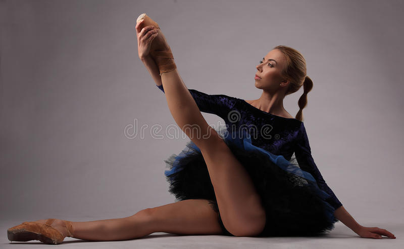 Красивая балерина в голубом обмундировании в студии сидит на поле и держит ее ногу стоковая фотография rf