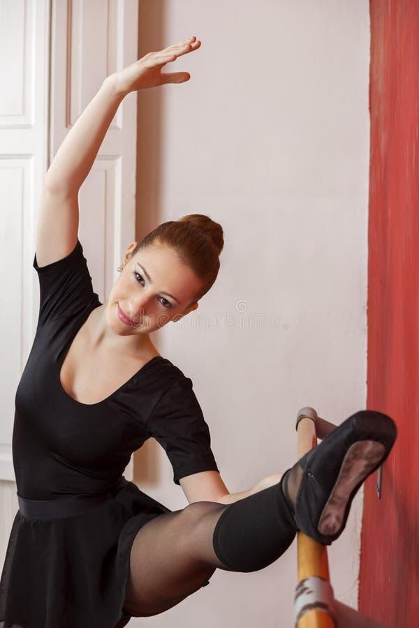 Красивая балерина практикуя на Barre в студии стоковое изображение rf
