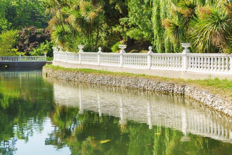 Красивая балюстрада и свое отражение в пруде парка города южного стоковое изображение