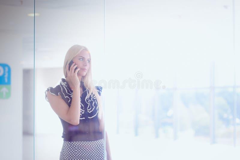 Красивая белокурая бизнес-леди говорит на телефоне стоковое фото