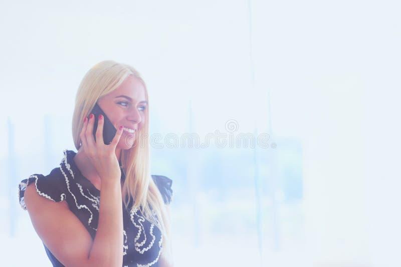 Красивая белокурая бизнес-леди говорит на телефоне стоковое фото rf