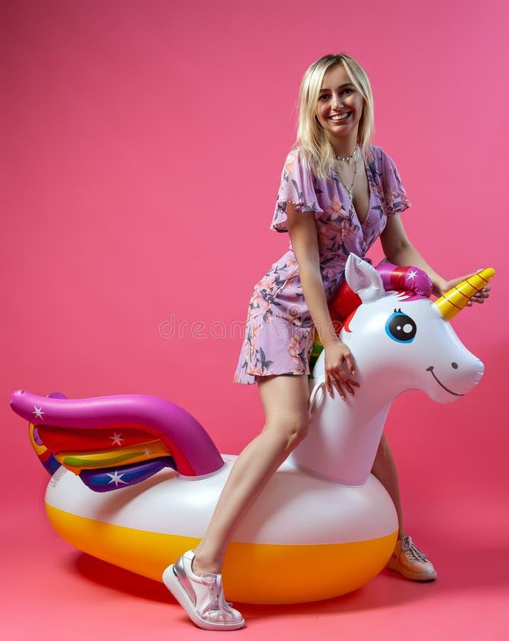 Красивая белокурая девушка в сексуальные sundress с тонкими ногами в белых тапках стоит на раздувном пестротканом единороге на a стоковые фото