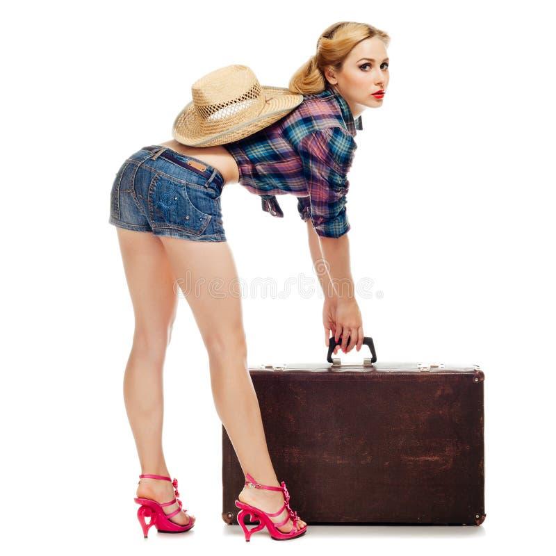 Красивая белокурая девушка в шортах checkered рубашки и джинсовой ткани пробует поднять старый чемодан с соломенной шляпой и усме стоковое фото rf