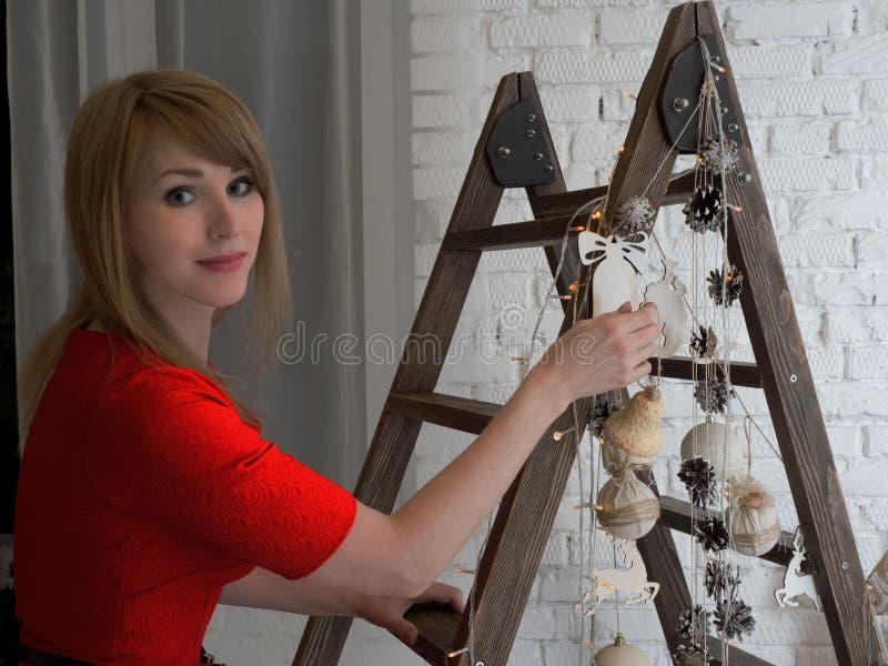 Красивая белокурая девушка в ` s Нового Года красного платья вися забавляется на декоративной лестнице стоковая фотография