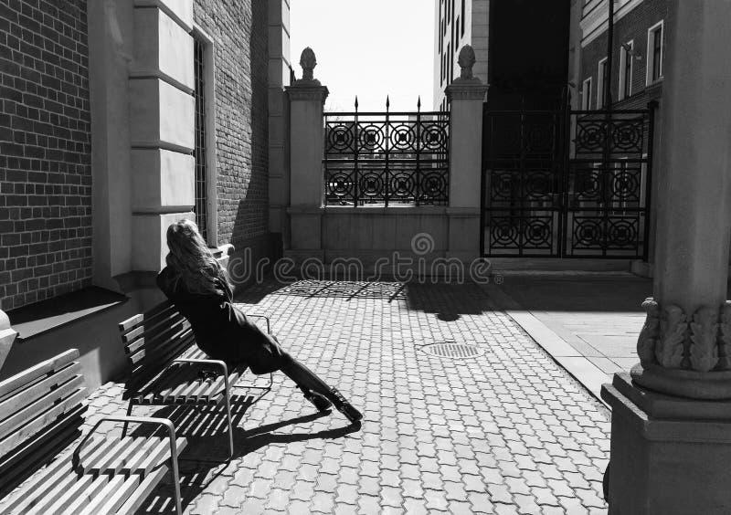 Красивая белокурая девушка нося красное пальто и перчатки сидит и отдыхает на стенде улицы около кирпичной стены и нанесенной заг стоковая фотография