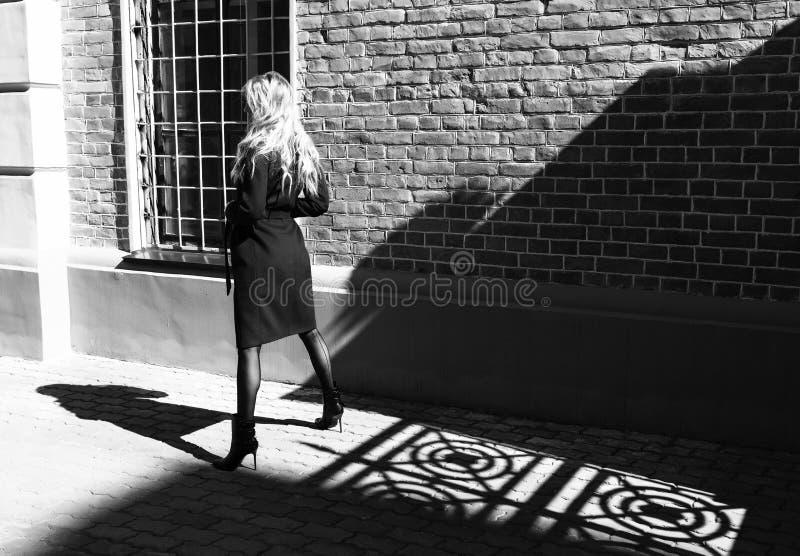 Красивая белокурая девушка нося красное пальто и стойки перчаток около тени нанесенной загородки на тротуаре Модный, стоковые фотографии rf