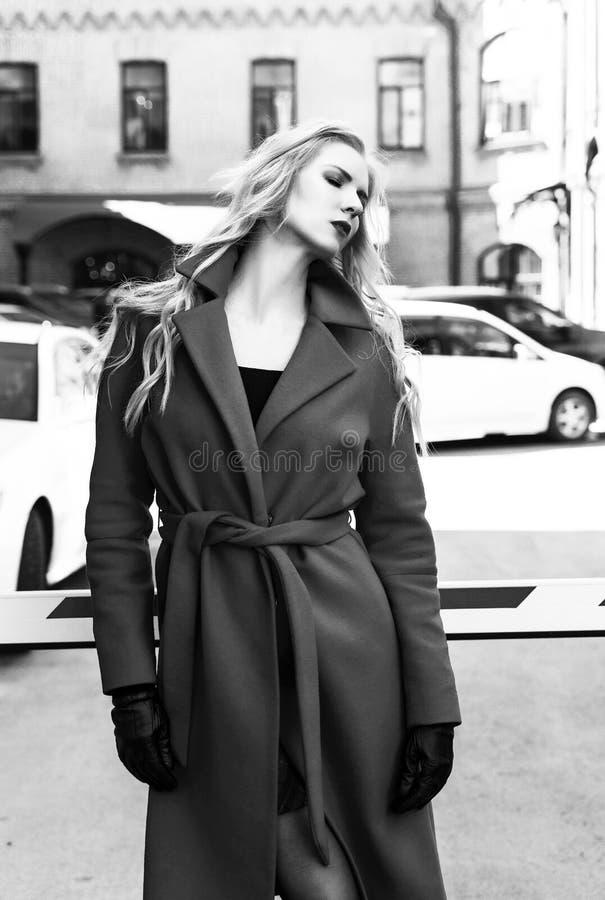 Красивая белокурая девушка нося красное пальто и стойки перчаток около барьера среди старых зданий Модный, промышленный, стоковые фотографии rf