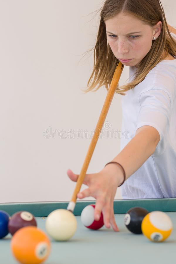Красивая белокурая девушка подростка играет billard, фокусируя и направляя к шарику стоковое изображение rf