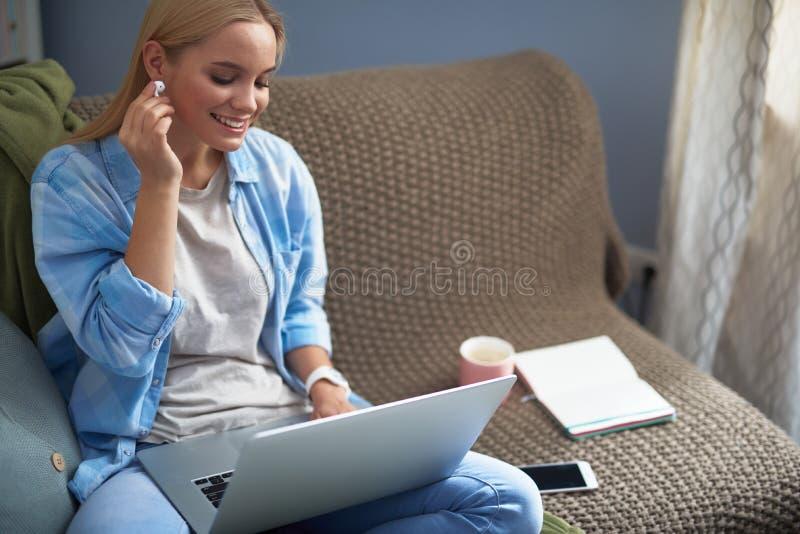 Красивая белокурая девушка с беспроводным наушником используя ноутбук дома стоковое фото rf