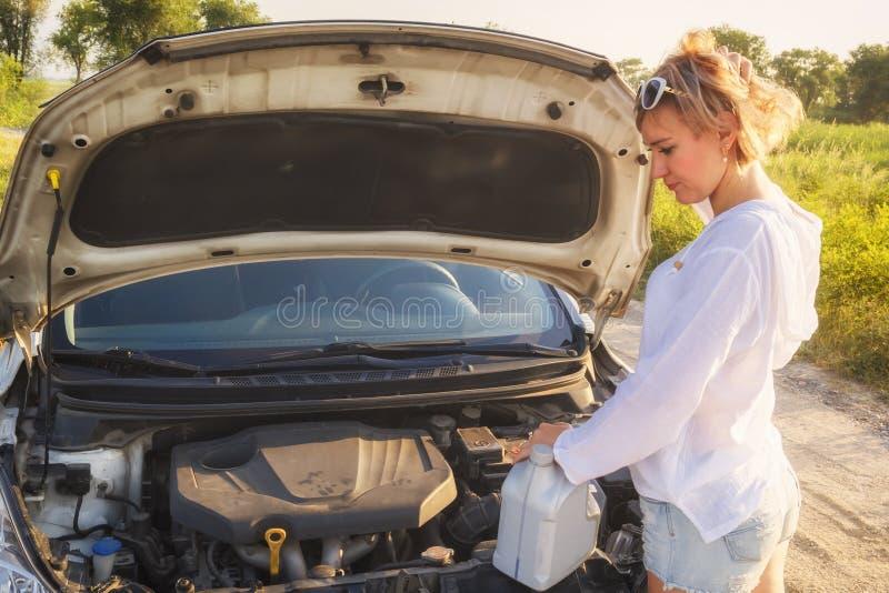 Красивая белокурая девушка с чонсервной банкой масла приниманнсяые за ремонты автомобиля на проселочной дороге и лучах заходящего стоковые изображения rf