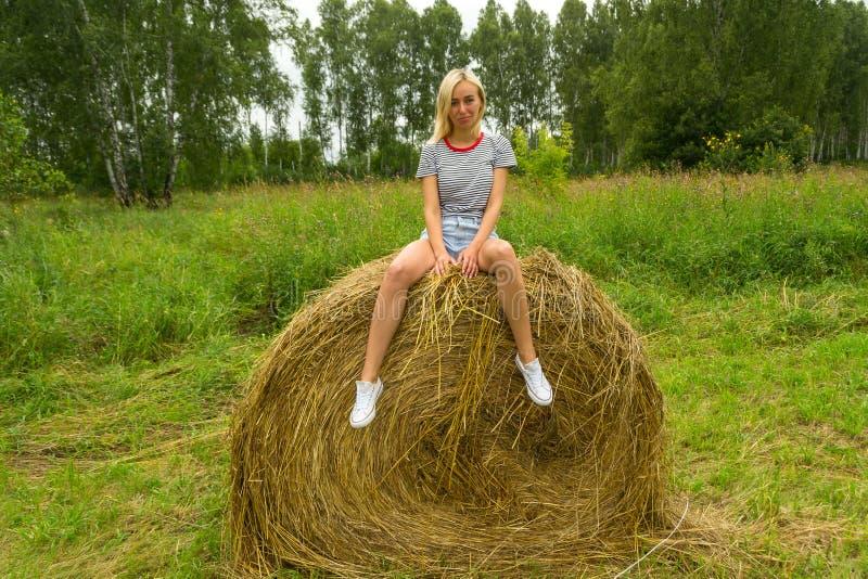 Красивая белокурая девушка усмехается и держится пук betwee травы стоковые изображения rf