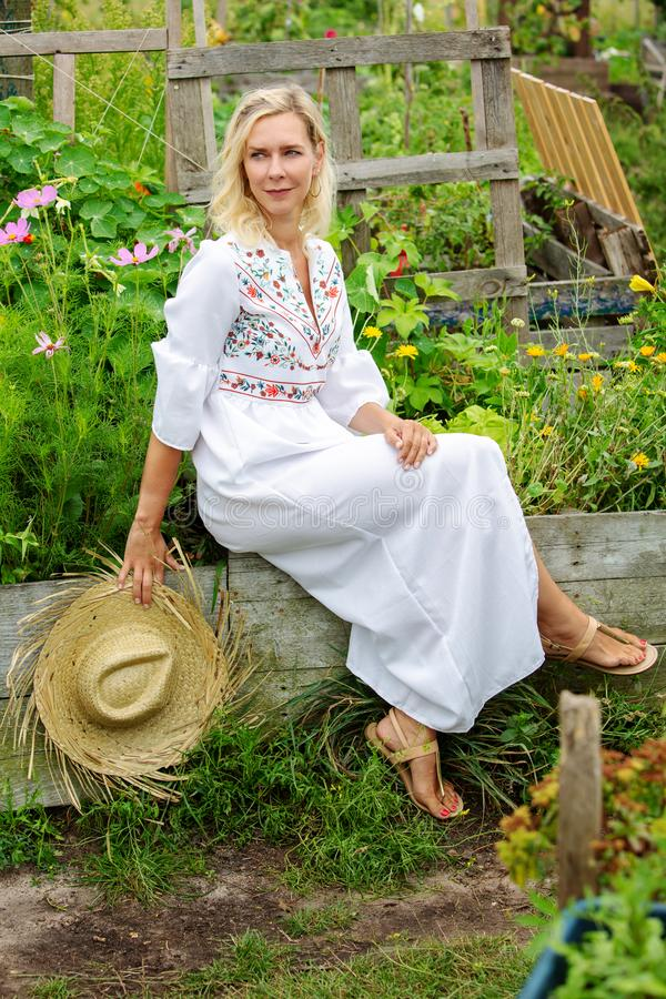 Красивая белокурая женщина в белом платье сидя снаружи в саде стоковая фотография