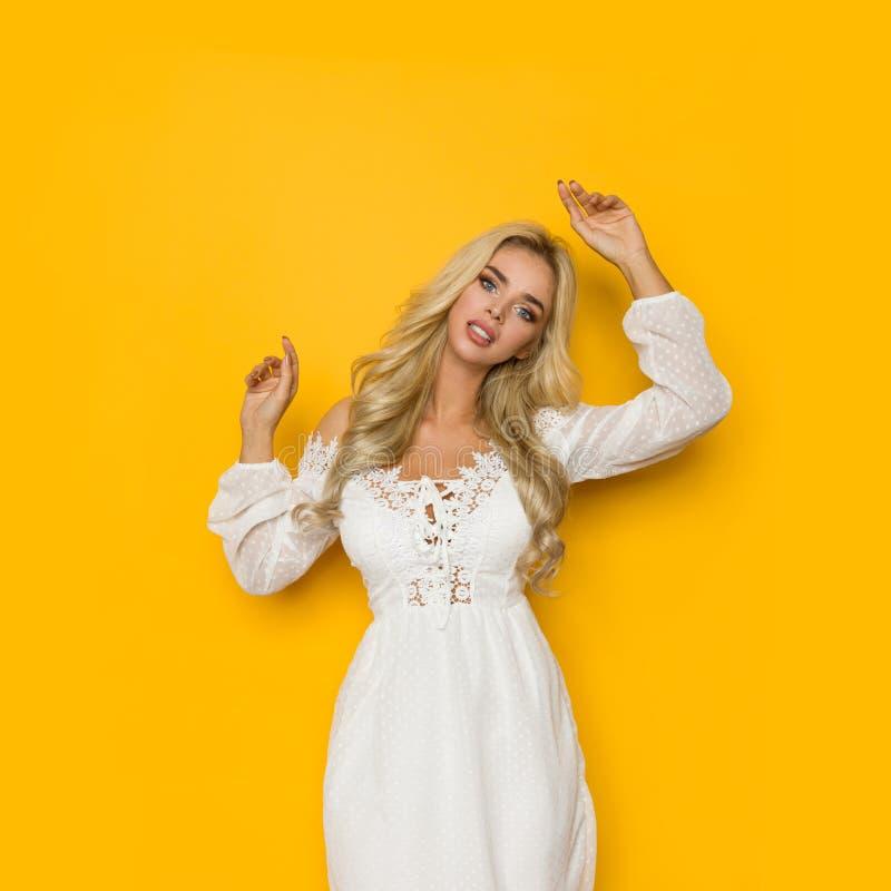 Красивая белокурая женщина в белом платье шнурка представляет с поднятыми оружиями стоковая фотография