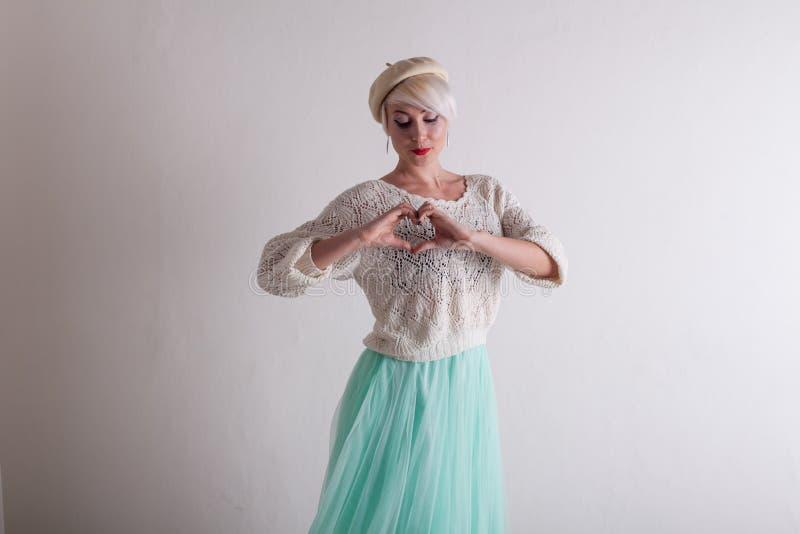 Красивая белокурая женщина в берете и ярком платье на белой предпосылке стоковая фотография rf