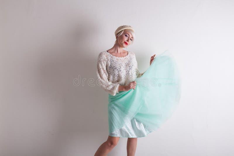 Красивая белокурая женщина в берете и ярком платье на белой предпосылке стоковое фото