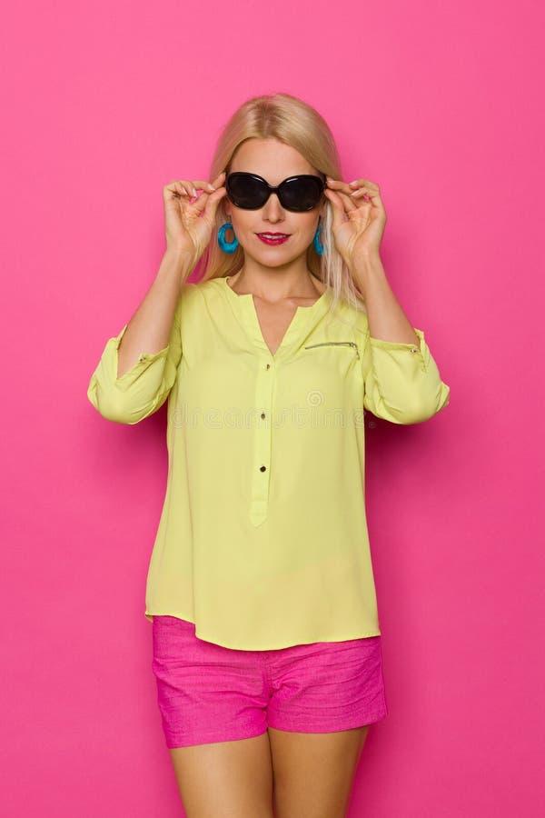 Красивая белокурая женщина в живых одеждах держит солнечные очки стоковые фото