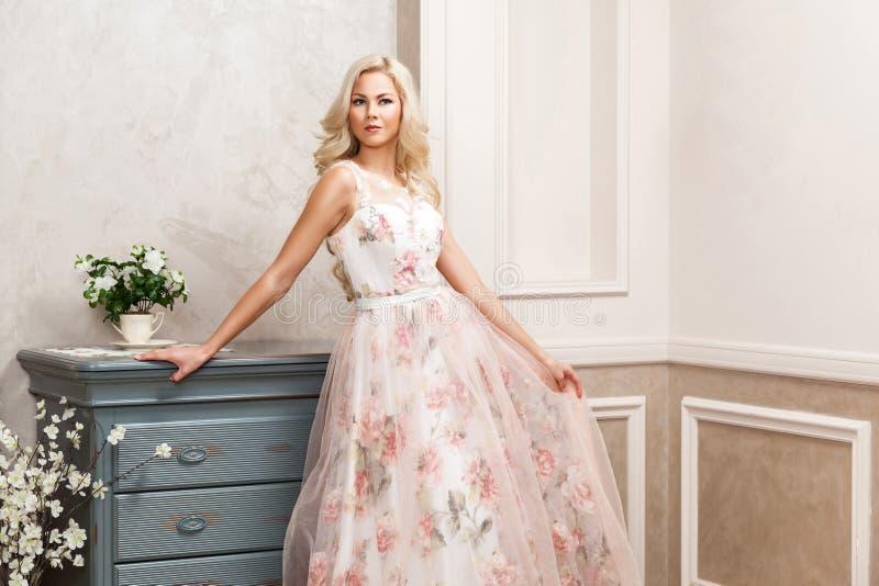 Красивая белокурая женщина в пастельном флористическом длинном тучном платье с макияжем и длинным курчавым стилем причесок полага стоковые фото