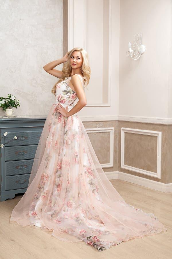 Красивая белокурая женщина в пастельном флористическом длинном тучном платье с макияжем и длинным курчавым положением стиля приче стоковое изображение rf