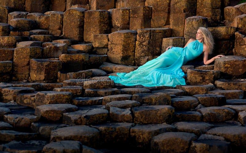 Красивая белокурая женщина в платье бирюзы длинном на мощеной дорожке Giants в северной Ирландии стоковая фотография rf