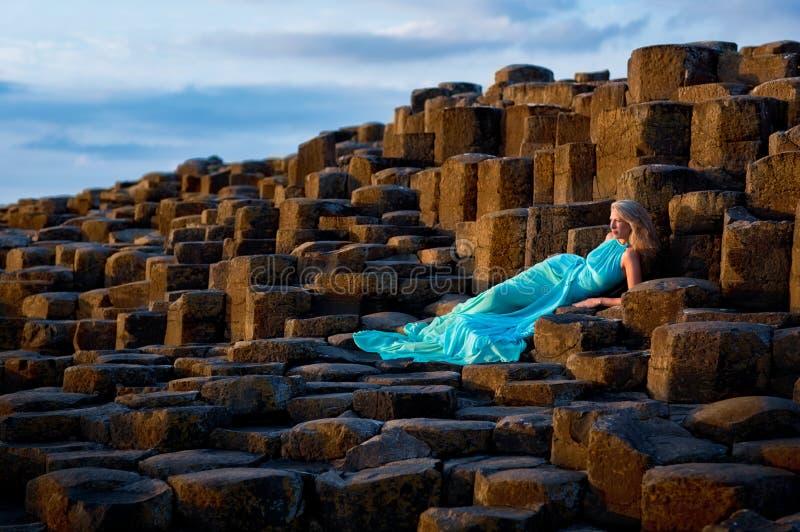 Красивая белокурая женщина в платье бирюзы длинном на мощеной дорожке Giants в северной Ирландии стоковые изображения