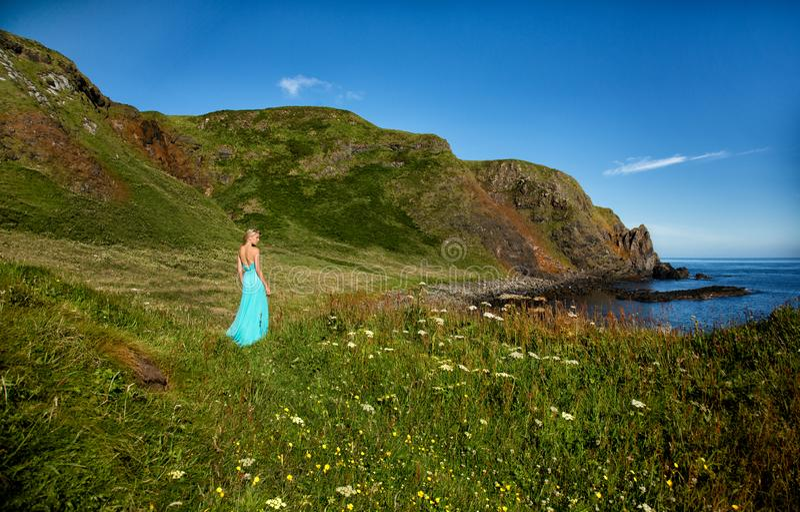 Красивая белокурая женщина в платье бирюзы зеленом длинном, стоит в середине поля, близко к морю, в Ирландии стоковая фотография rf