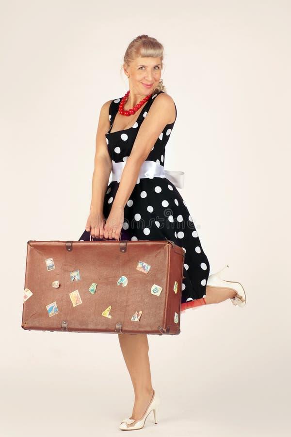 Красивая белокурая женщина в стиле pinup одетая в платье полька-точки стоит и flirtatiously держит коричневый чемодан, белый стоковое фото rf