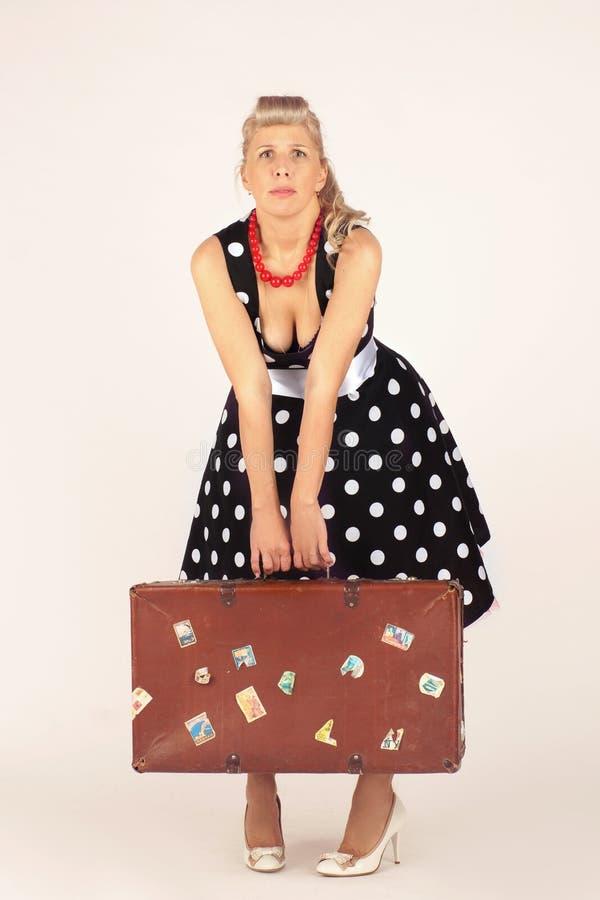Красивая белокурая женщина в стиле pinup, одетом в платье полька-точки, стойки и едва ли держит тяжелый чемодан, белую предпосылк стоковое изображение