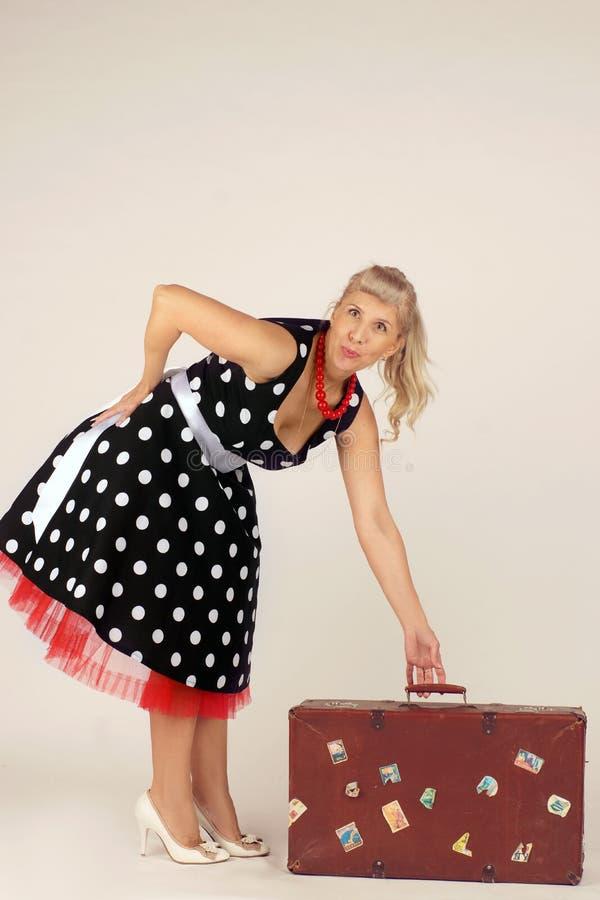 Красивая белокурая женщина в стиле pinup, одетом в платье полька-точки, стоит и поднимает чемодан перемещения, белая предпосылка стоковое изображение rf