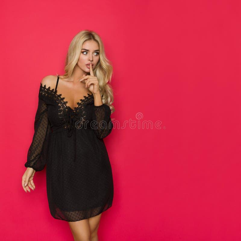 Красивая белокурая женщина в черном платье шнурка держит указательный палец на губах и смотрит прочь стоковое фото rf