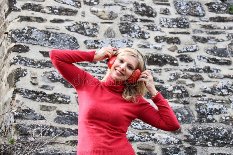 Красивая белокурая женщина в wi музыки красного свитера усмехаясь слушая стоковые изображения