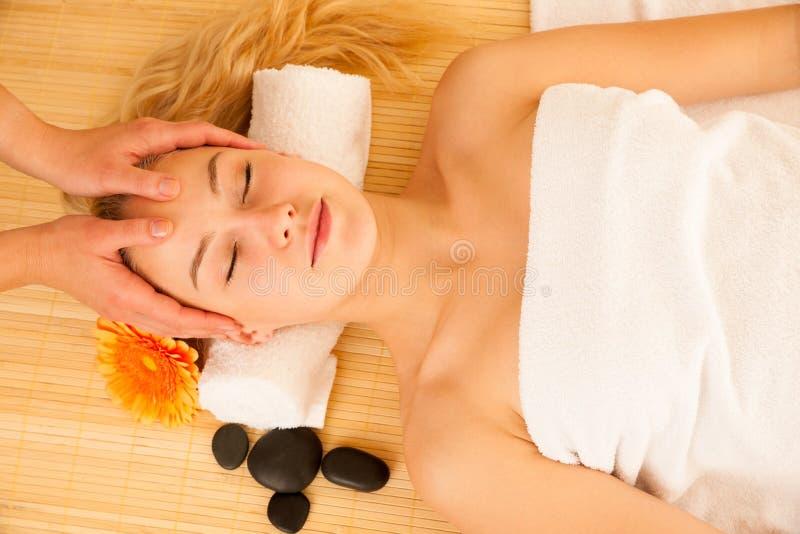 Красивая белокурая женщина имея массаж стороны в салоне курорта стоковые фото
