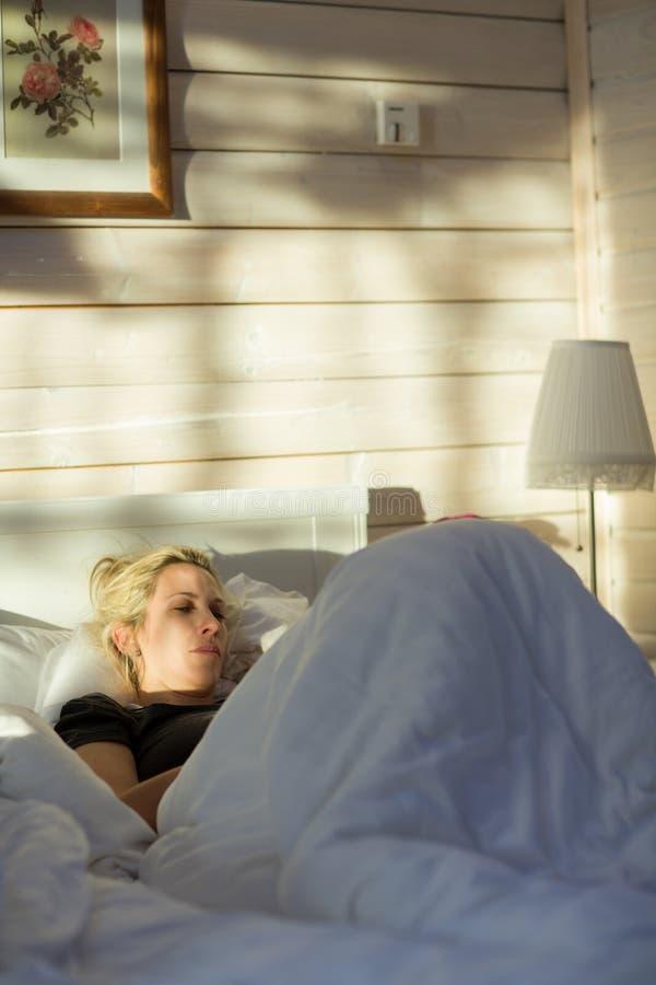 Красивая белокурая женщина кладет и читает внутри кровать стоковые изображения rf