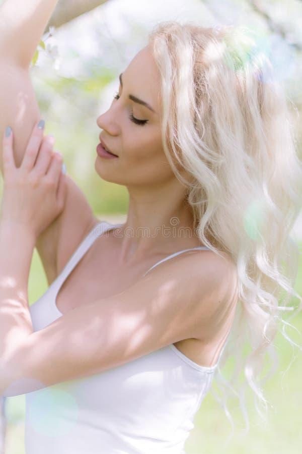 Красивая белокурая женщина наслаждается в зацветая саде стоковое фото rf
