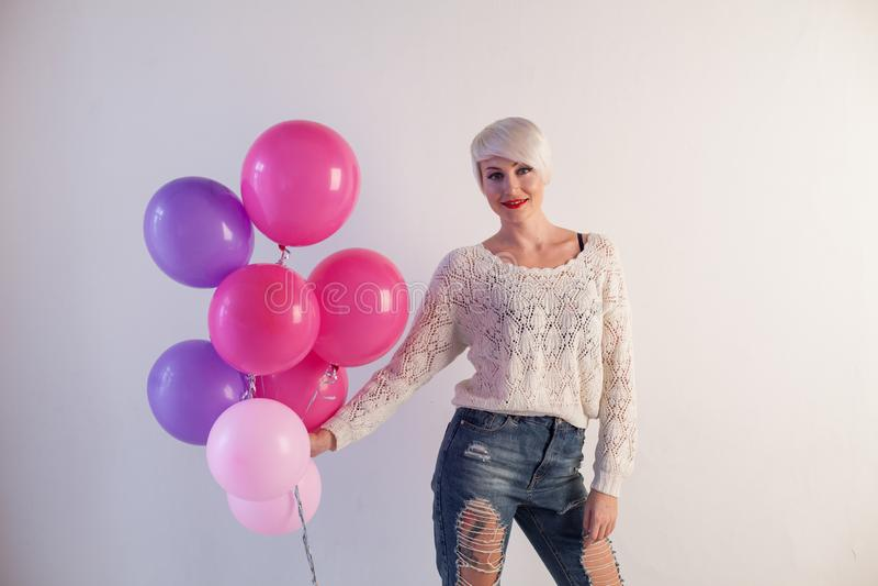 Красивая белокурая женщина на празднике с подарками и воздушными шарами стоковое изображение rf