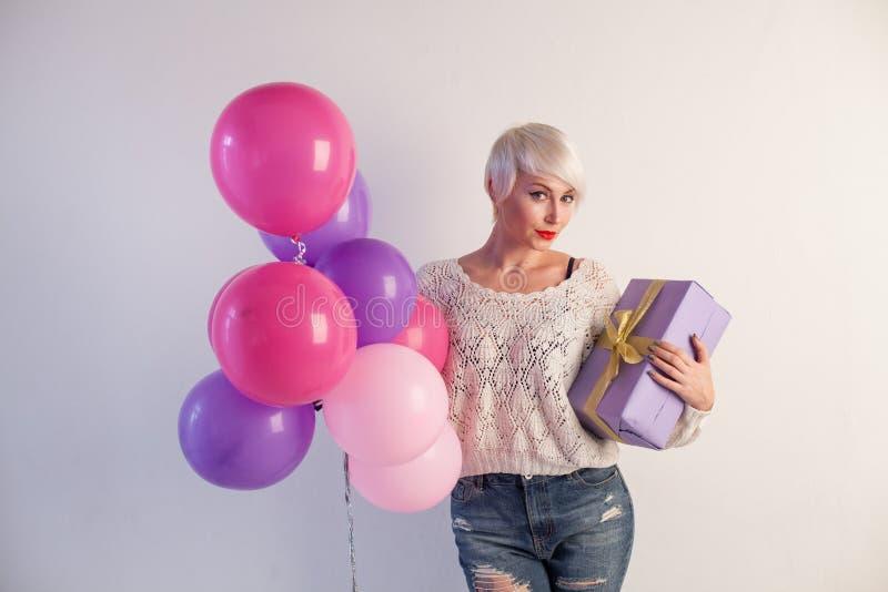 Красивая белокурая женщина на празднике с подарками и воздушными шарами стоковое фото rf