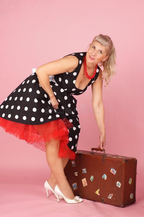 Красивая белокурая женщина поднимая чемодан и усмехаясь, стиль штыря-вверх на розовой предпосылке стоковое фото