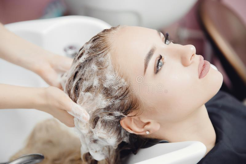 Красивая белокурая женщина получая мытье волос в салоне красоты стоковая фотография