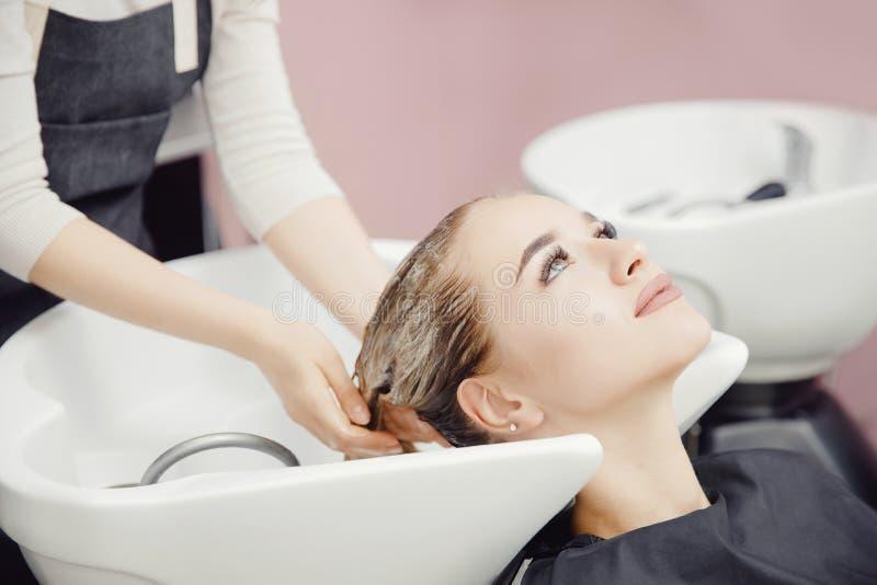 Красивая белокурая женщина получая мытье волос в салоне красоты стоковые фотографии rf