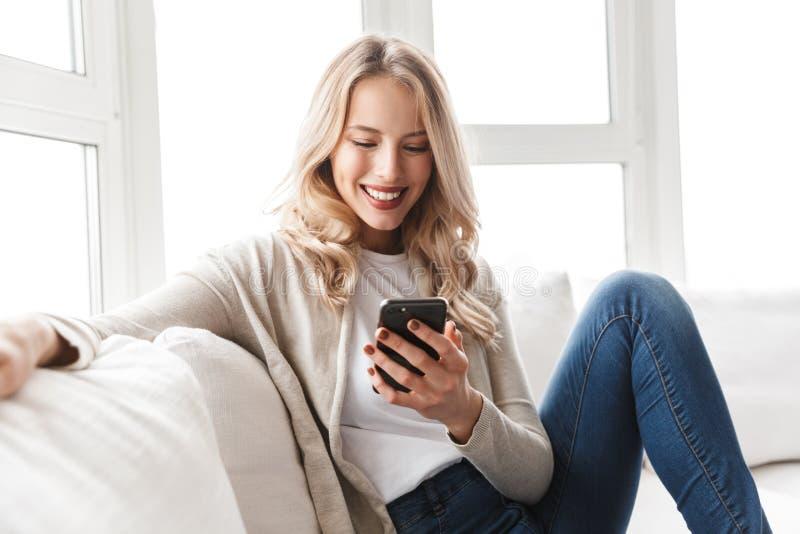 Красивая белокурая женщина представляя сидеть внутри помещения дома используя мобильный телефон стоковые фотографии rf