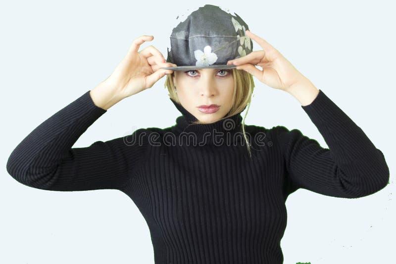 Красивая белокурая женщина при черный turtleneck и в стиле фанк флористическая шляпа держа оправу стоковое фото