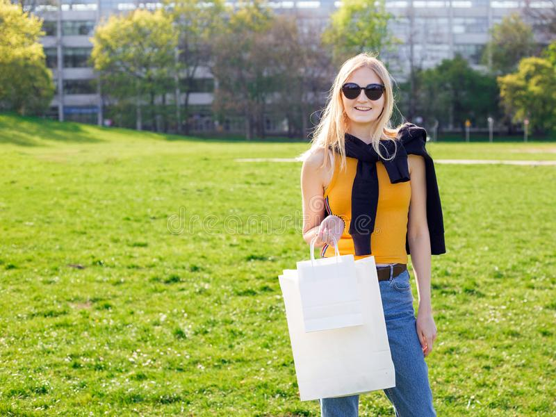 Красивая белокурая женщина с солнечными очками наслаждается покупками Защита интересов потребителя, ходя по магазинам насмешка вв стоковое изображение