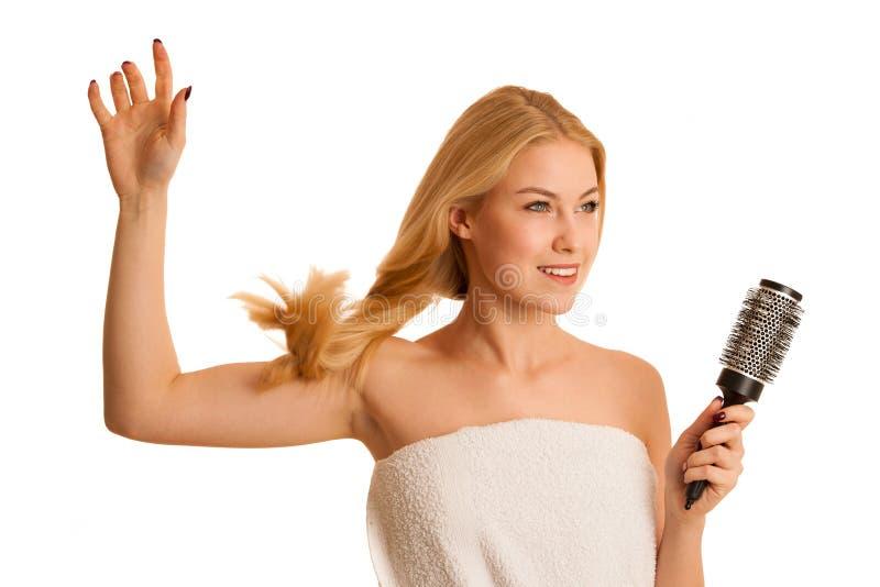 Красивая белокурая женщина чистя ее волосы щеткой как уход за волосами og знака стоковые изображения