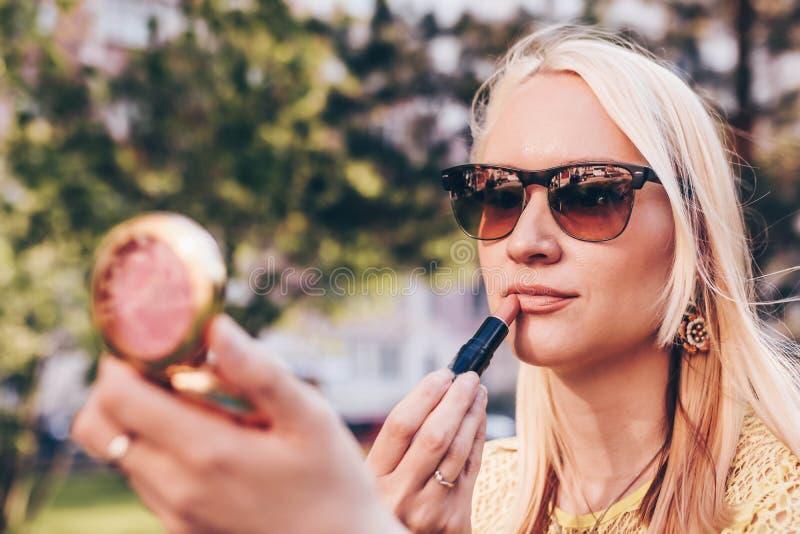 Красивая белокурая женщина loking в небольшом зеркале и покрасила ее губы Концепция макияжа в улице стоковое фото